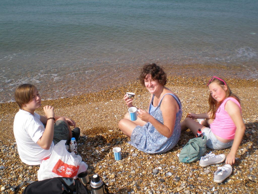 Ruth and the kids having a picnic on the beach